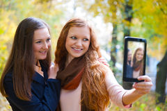 Two girls taking picture with digital tablet Stock Image