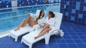 Two beautiful girls taking selfies next to swimming pool stock footage