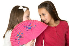 Two beautiful girls talking behind oriental fan whisper playing Stock Photos