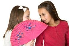 Two beautiful girls talking behind oriental fan whisper playing Stock Photos