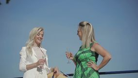 Two beautiful girls talking at blue sky background. Two beautiful girls hold champagne in hands and talking. Pretty ladies stand at blue sky background. The stock video footage