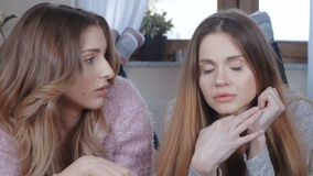 Two beautiful girls talking while lying on bed. Two girl friends or sisters, blond and brunette gossip and share secrets stock video footage