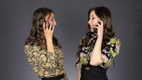 Two beautiful girls talking on the phone. Smile and beauty stock video footage