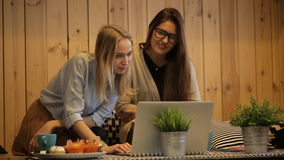 Two beautiful girls talking and use laptop. In cafe stock footage