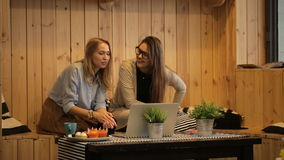 Two beautiful girls talking and use laptop stock video