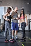 Two beautiful girls with their coach browsing something in the smartphone in modern fitness club stock photo