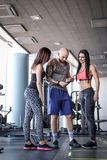 Two beautiful girls with their coach browsing something in the smartphone in modern fitness club. Two beautiful girls with their coach browsing something in the royalty free stock photography