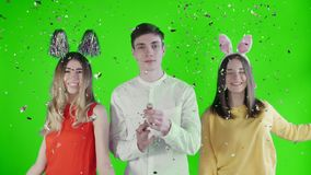 Two beautiful girls throw confetti and young man Exploding party popper on green screen stock video footage