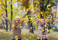 Two beautiful girls throwing autumn leaves in the air. Two beautiful girls throwing leaves in the air in autumn forest Stock Photo