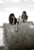 Two beautiful girls on the top of a roll, in a field. Stock Photo