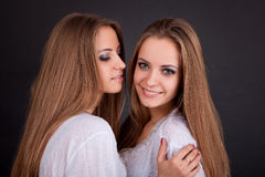 Two beautiful girls twins, isolated on black Stock Photo