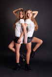 Two beautiful girls twins, isolated on black Royalty Free Stock Photo