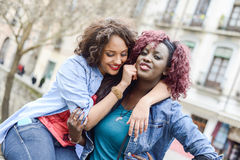 Two beautiful girls in urban backgrund, black and mixed women. Portrait of two beautiful girls in urban backgrund, black and mixed women. Friends talking stock photo