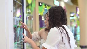 Two beautiful girls use the interactive panel while making an online purchase at the mall. Two beautiful young girls use an interactive panel while making an stock video