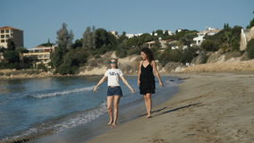 Two beautiful girls are walking along the beach near the ocean. Pretty friends are laughing and talking. Young curly brunette and cute blonde in sunglasses stock video footage
