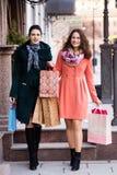 Two beautiful girls walking down the street while shopping. Two beautiful smiling girls walking down the street while shopping royalty free stock photography