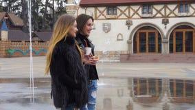 Two beautiful girls walking and talking stock video footage