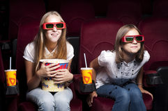 Two beautiful girls watching a movie at the cinema. Two girls look three-dimensional cinema, sitting in the glasses, eat popcorn, drink drink Royalty Free Stock Photography