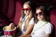 Two beautiful girls watching a movie at the cinema. Two girls look three-dimensional cinema, sitting in the glasses, eat popcorn, drink drink Stock Photo