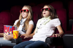 Two beautiful girls watching a movie at the cinema. Two girls look three-dimensional cinema, sitting in the glasses, eat popcorn, drink drink Stock Photography