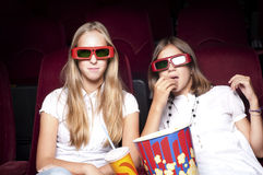 Two beautiful girls watching a movie at the cinema. Two girls look three-dimensional cinema, sitting in the glasses, eat popcorn, drink drink Royalty Free Stock Image