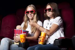 Two beautiful girls watching a movie at the cinema Stock Photography
