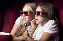 Two beautiful girls watching a movie at the cinema. Two girls look three-dimensional cinema, sitting in the glasses, eat popcorn, drink drink Royalty Free Stock Photo