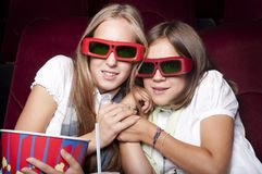 Two beautiful girls watching a movie at the cinema Stock Images