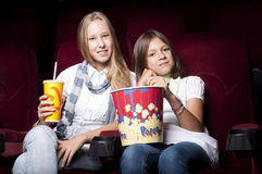 Two beautiful girls watching a movie at the cinema. Two girls look three-dimensional cinema, sitting in the glasses, eat popcorn, drink drink Stock Image
