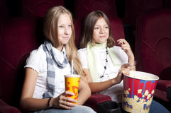 Two beautiful girls watching a movie at the cinema. Two girls look three-dimensional cinema, sitting in the glasses, eat popcorn, drink drink Royalty Free Stock Images