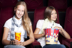 Two beautiful girls watching a movie at the cinema Royalty Free Stock Photo