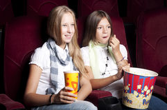 Two beautiful girls watching a movie at the cinema Stock Photo