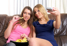 Two beautiful girls watching TV. Two beautiful girls watching some interesting on TV Royalty Free Stock Photography