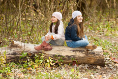 Two Beautiful girls wearing a beret sitting on log posing Stock Photography