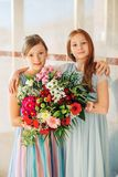 Two beautiful girls wearing occasional dresses. Two beautiful girls wearing occasion dresses, holding big flower bouquet stock photos