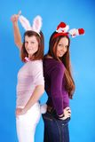 Two beautiful girls wearing santa claus clothes. Royalty Free Stock Photo