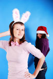 Two beautiful girls wearing santa claus clothes. Royalty Free Stock Images
