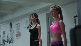 Two beautiful girls in the weights at the gym. 4k. Two young sporty woman in the gym centre stock video footage