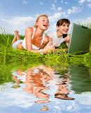 Two beautiful girls in white clothes. Are laughing and looking at laptop computer outdoors. Lay on the green grass. Reflected in water Royalty Free Stock Image