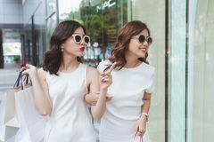 Two beautiful girls window shopping in the city royalty free stock photos