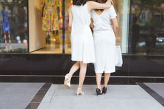 Two beautiful girls window shopping in the city stock images