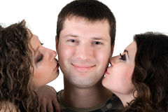 Two beautiful girls and young man. Two beautiful girls kiss the young man Stock Photo