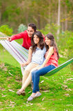 Two beautiful girls and a young man in hammock Royalty Free Stock Photo
