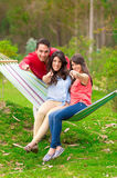 Two beautiful girls and a young man in hammock Stock Images