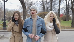 Two beautiful girls and a young man are walking along the street. Blonde and brunette talking on the phone, the guy does stock footage