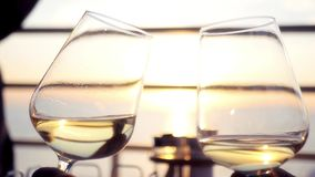 Two beautiful glass wine glasses with wine on a sunset background at sea. HD, 1920x1080. slow motion. Two beautiful glass wine glasses with wine on a sunset stock video
