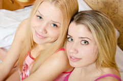 Two beautiful green & blue eyes blond sisters cute girlfriends in pink pajamas  happy smiling & looking at camera. Closeup portrait of 2 beautiful blonde young Stock Photo
