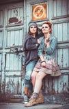 Two beautiful grunge girls standing at wall Royalty Free Stock Photo