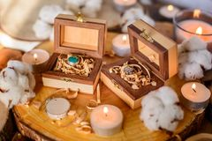 Wooden boxes with rings. Two beautiful handmade wooden boxes with rings on wooden background with candles and cotton flowers Stock Photography