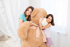 Two beautiful happy girls embracing huge plush bear Stock Photo